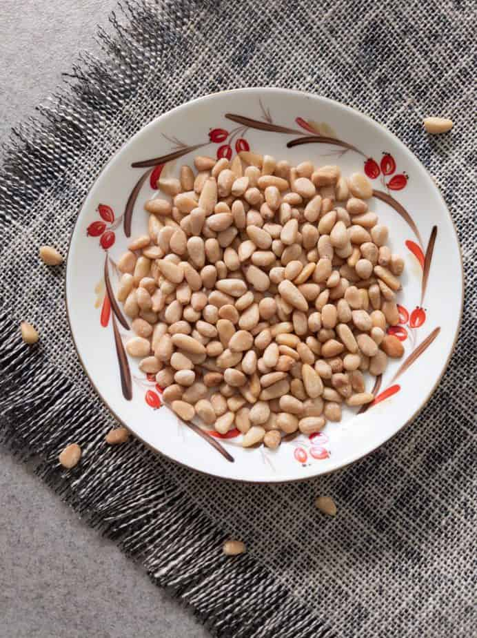 Toasted pine nuts on a plated decorated with red berries.