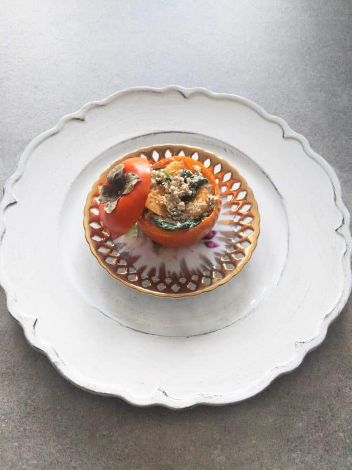 Japanese persimmon shiraae served in a persimmon bowl on a golden plate and white charger.