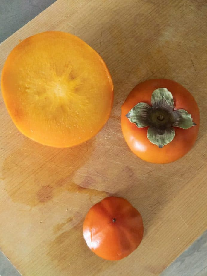 A persimmon with the top and bottom cut off.