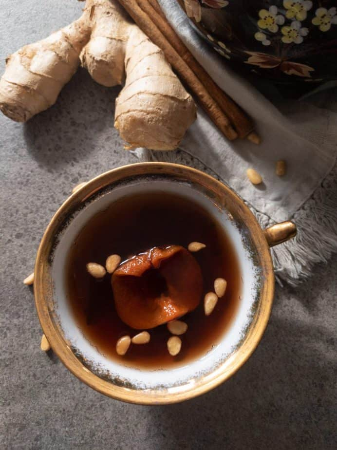 A cup of sujeonggwa with dried persimmon and toasted pine nuts, near ginger root and cinnamon sticks.