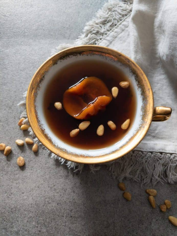 A cup of sujeonggwa with dried persimmon and toasted pine nuts.