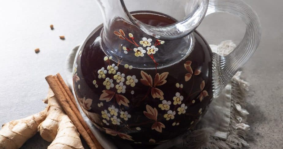 A pitcher of sujeonggwa beside cinnamon sticks, ginger root, and pine nuts.