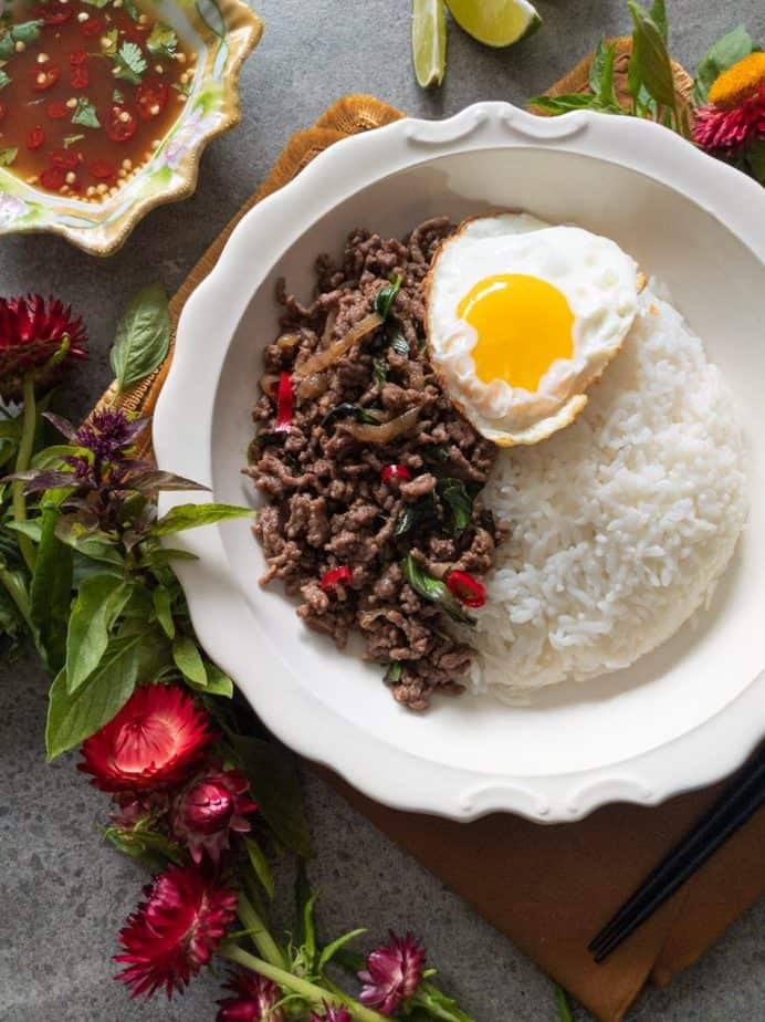 Thai basil beef stir fry with a Thai-style fried egg in a white bowl, surrounded by red flowers.