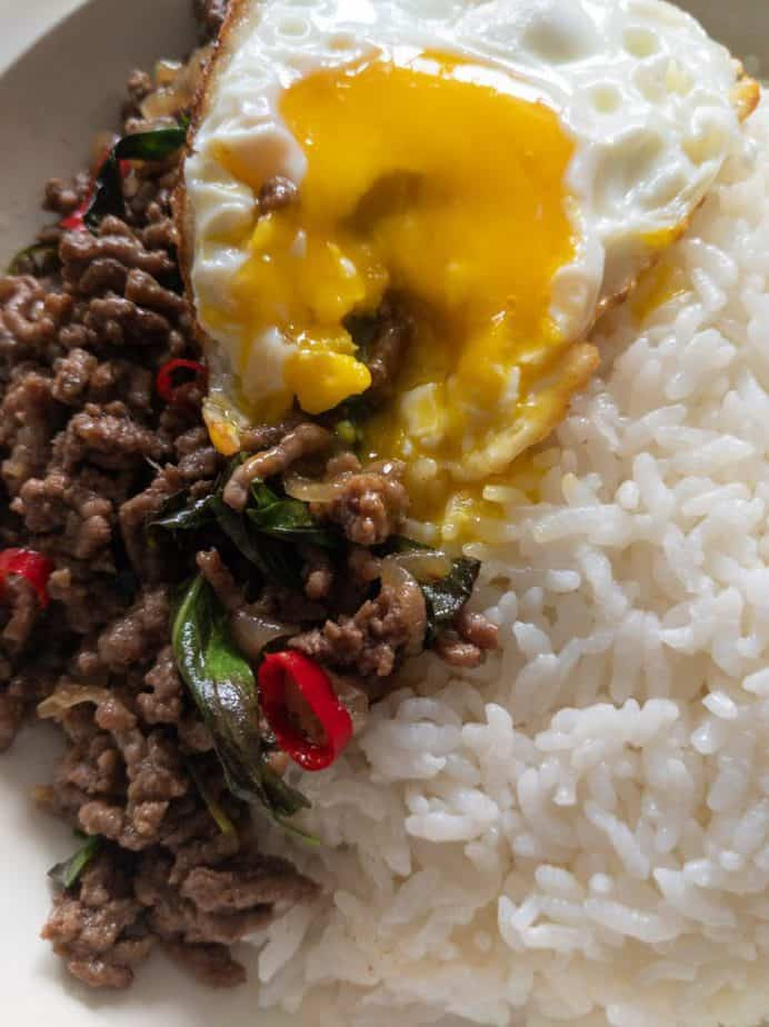 A runny Thai-style fried egg on top of pad gra pow.