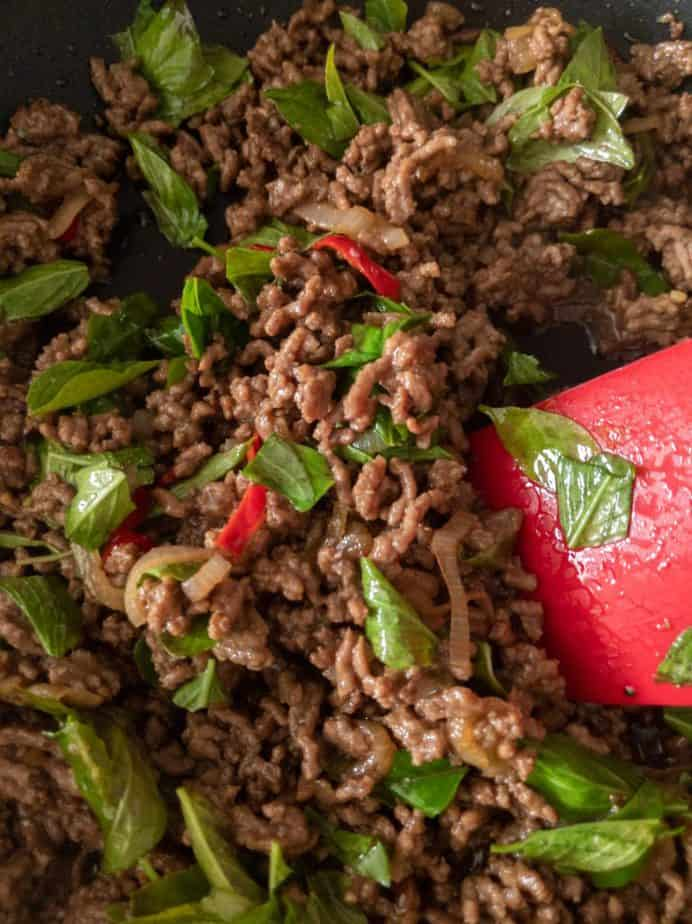 A red spatula stirring torn Thai basil into a beef stir fry.