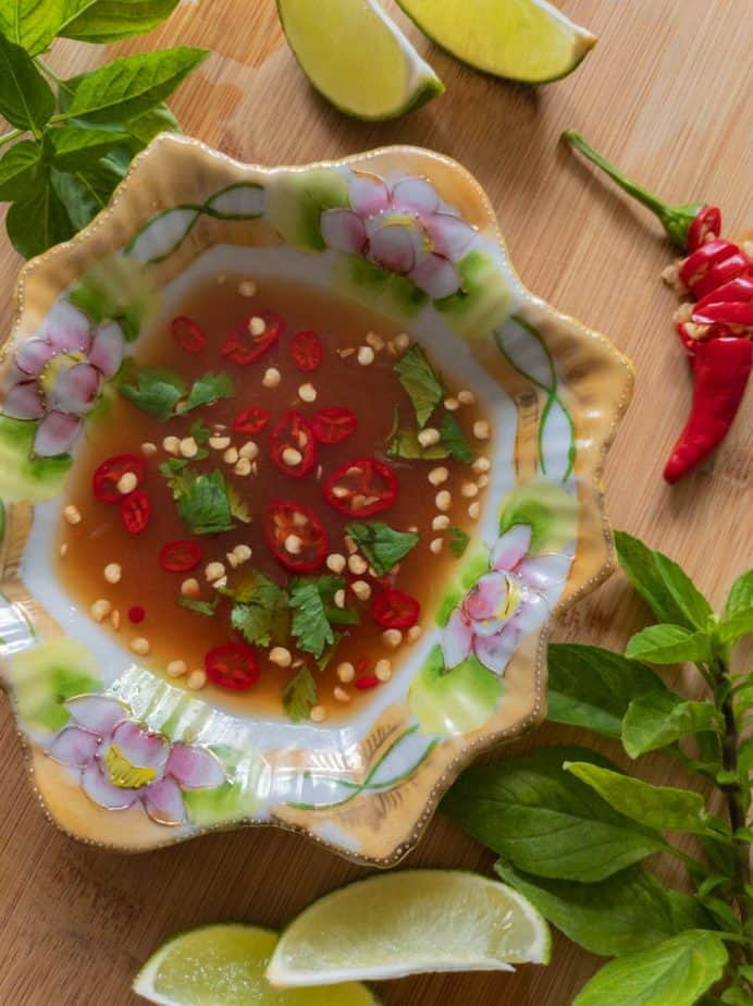 A lotus decorated bowl of traditional Thai sauce beside lime wedges, Thai basil, and sliced chilis.