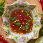 A lotus decorated bowl of traditional Thai sauce beside lime wedges and sliced chilis.