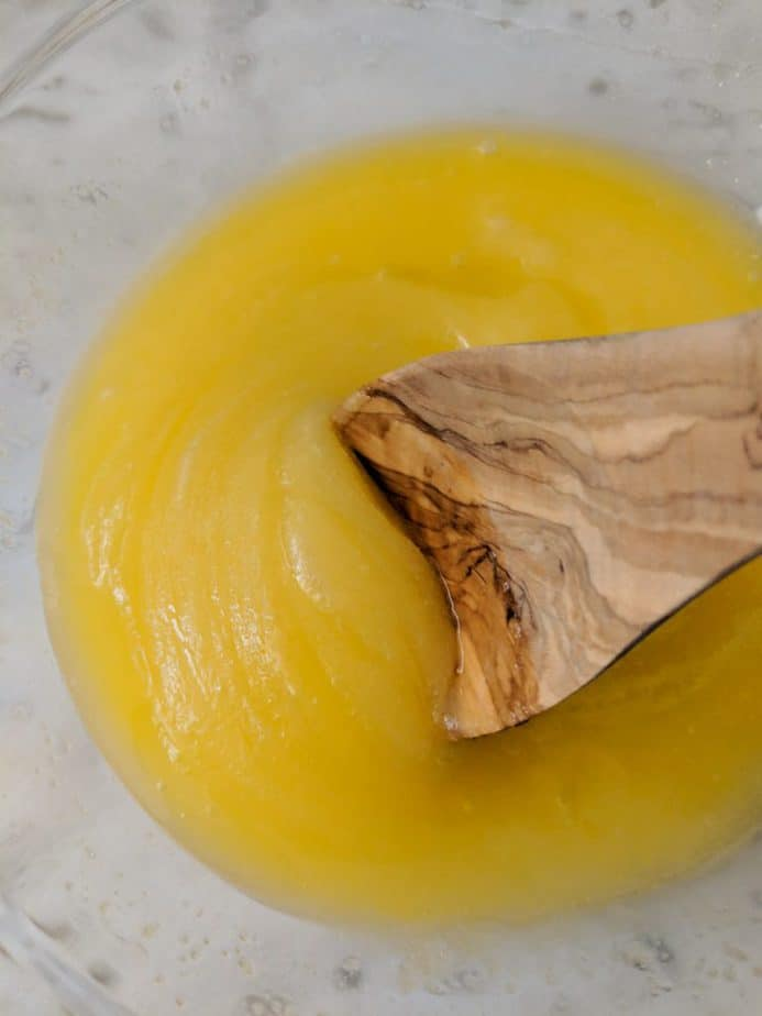Wooden spoon mixing melted butter, egg, and sugar