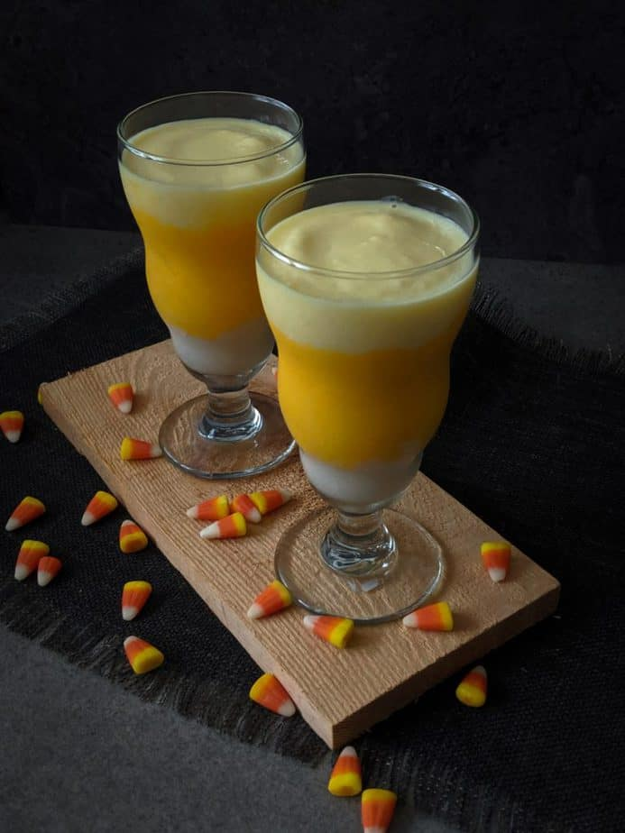 Two candy corn smoothies surrounded by candy corn.