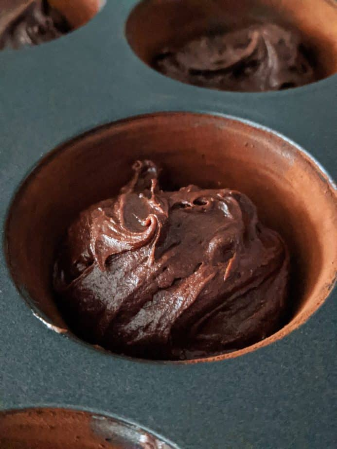 Brownie cupcake batter in a cocoa lined cupcake tin.