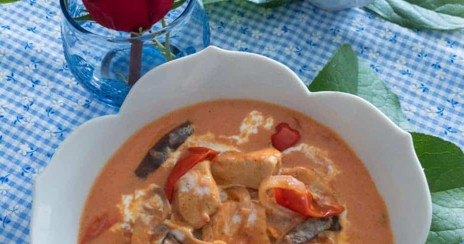 Creamy tomato chicken in a white, flower-shaped bowl on a checkered blue and white tablecloth.