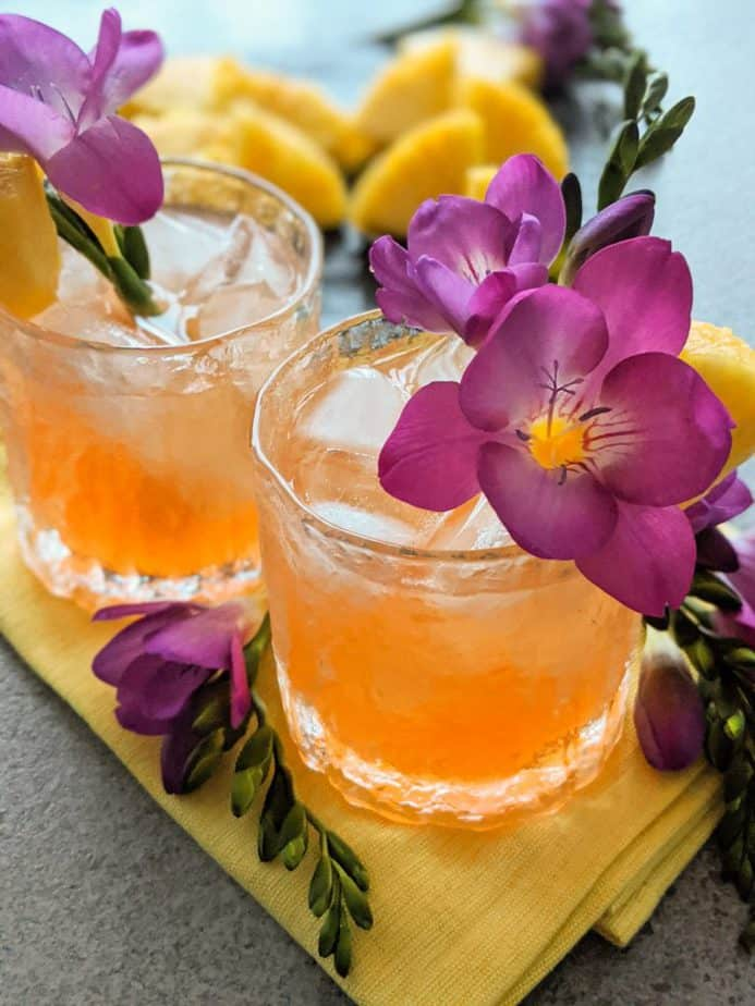 A couple east 8 hold up cocktails garnished with purple flowers.