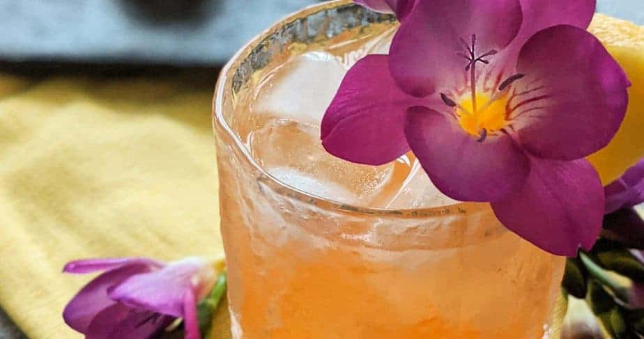 The east 8 hold up in a glass with purple flowers and pineapple wedges.