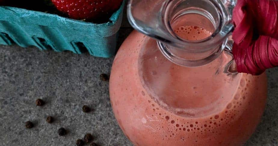 An overhead shot of a carafe of fresh strawberry vinaigrette.