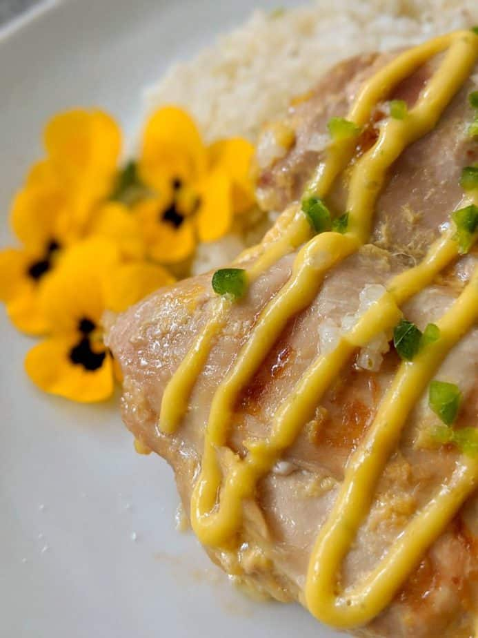 Mango lime chicken beside edible flowers