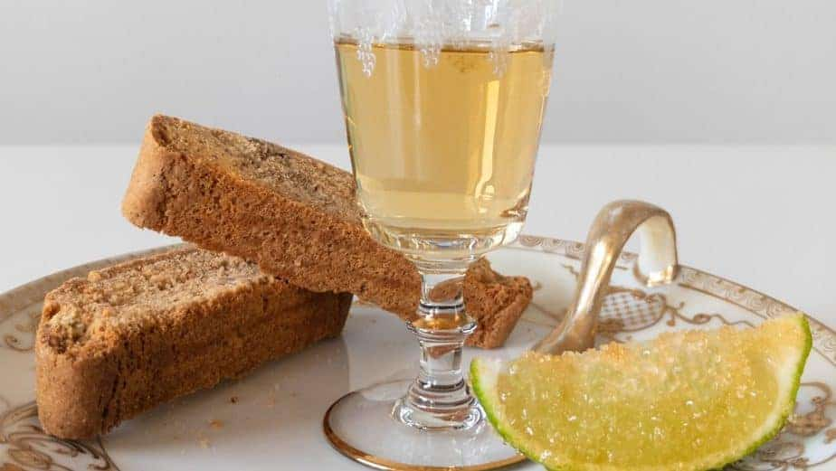 The Italian biscuit shot on a plate with a sugared lime and biscotti.