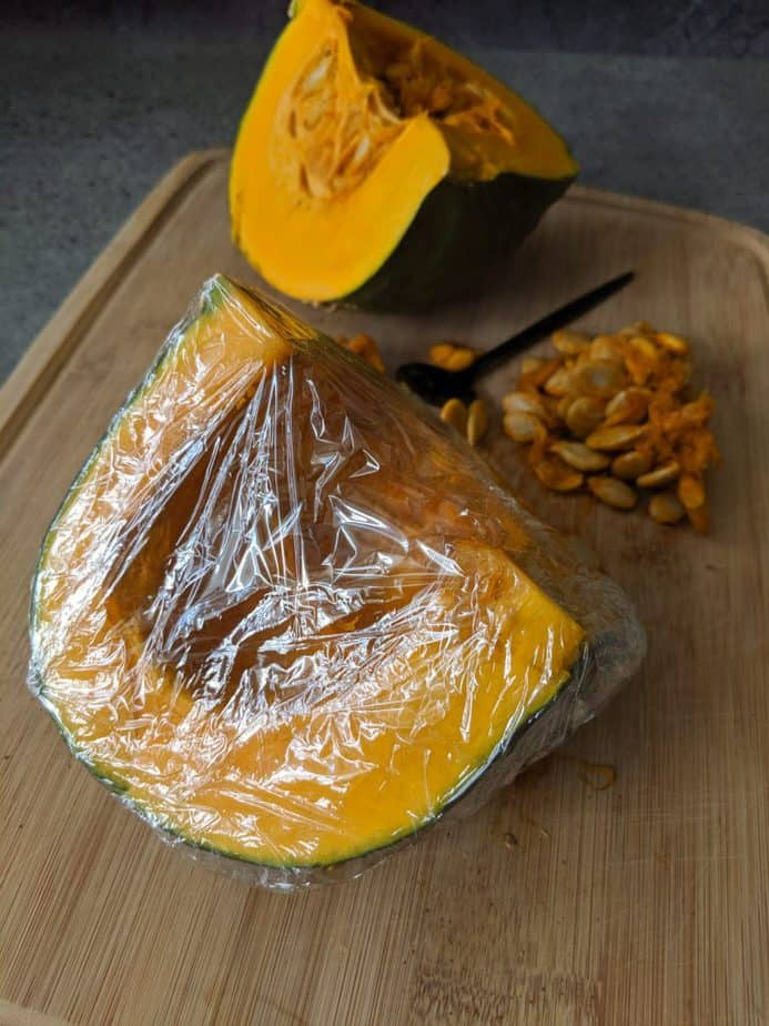 A quarter of kabocha squash, seeded and wrapped in plastic wrap.