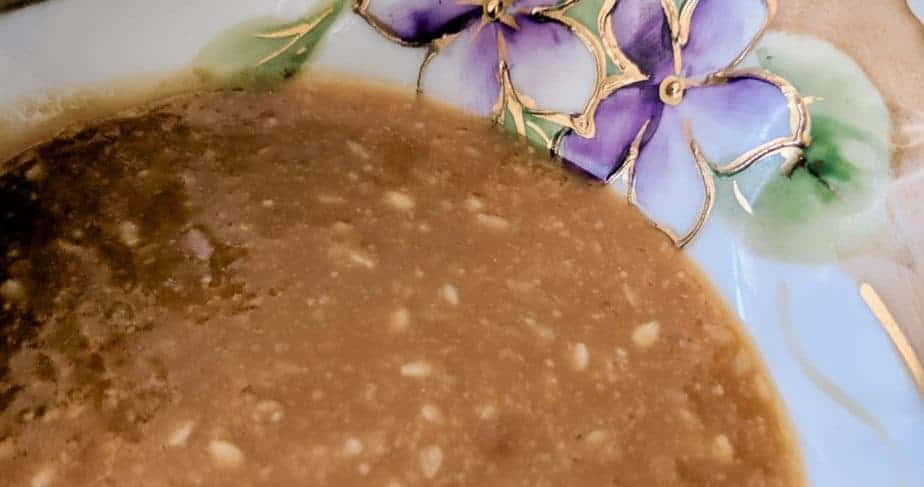 A close up of sesame sauce in a bowl decorated with flowers