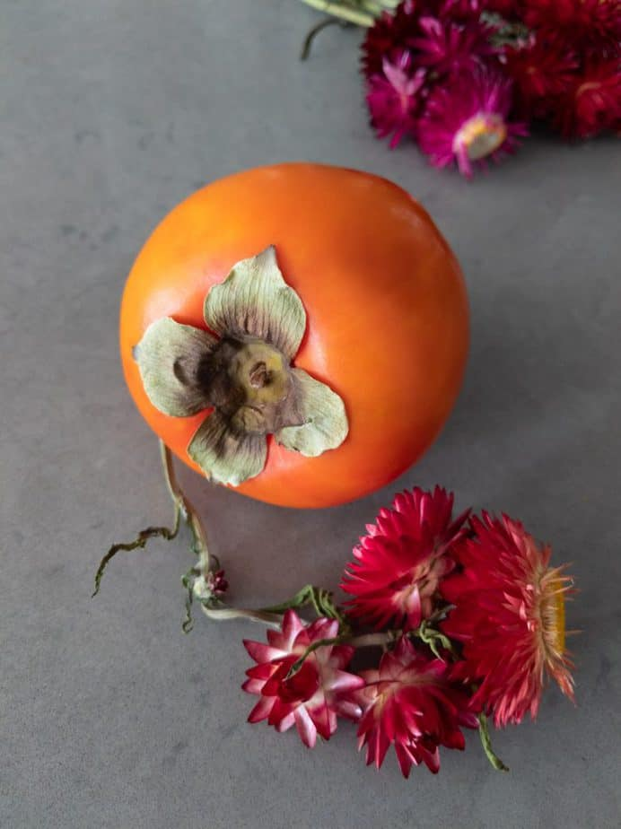 A persimmon and red flowers.