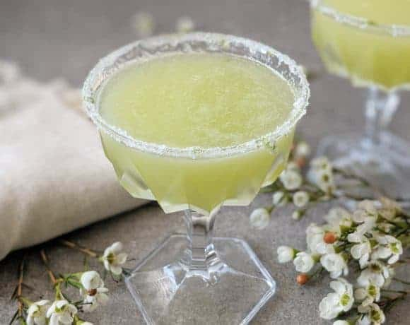 A melon margarita surrounded by white flowers.