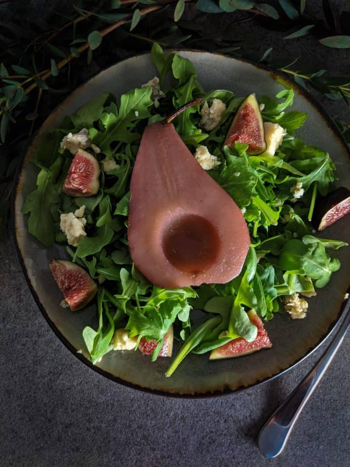 The pear is set on a salad bed of arranged arugula, figs, and stilton.