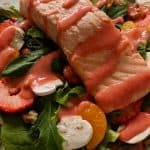 Poached salmon salad on a white plate.