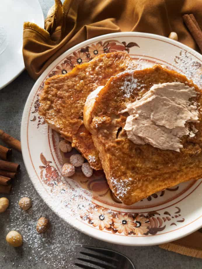 Two slices of pumpkin french toast with cinnamon sugar butter and hazelnuts on a brown floral plate.