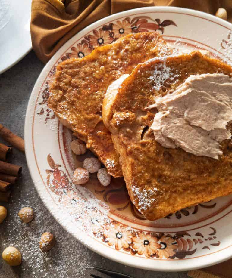 Slices of pumpkin french toast with cinnamon sugar butter, served on a brown floral plate, and surrounded by cinnamon sticks and toasted hazelnuts.