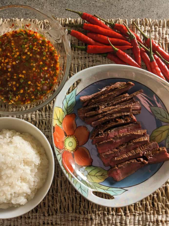 Sliced crying tiger steak on a floral dish served with white rice and dipping sauce.