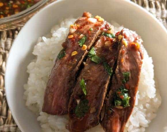 Strips of Thai crying tiger steak on a bowl of sticky rice.