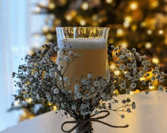 resh pear and almond cocktail in a glass decorated with baby's breath flowers.