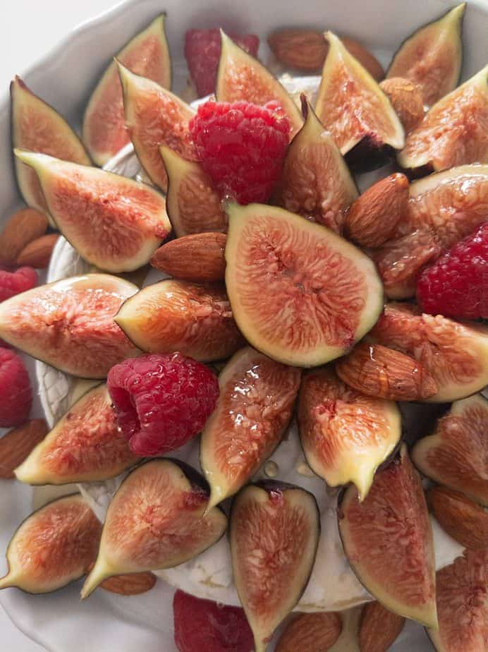 A close up of a baked brie covered with figs, raspberries, almonds, and truffled honey.