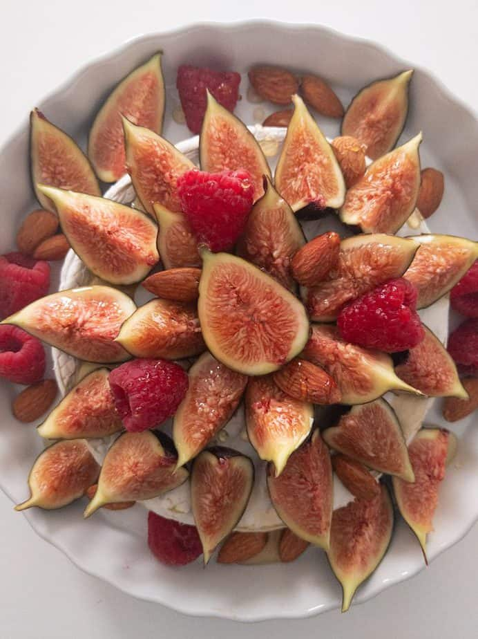An overhead shot of a baked brie covered with figs, raspberries, almonds, and truffled honey.