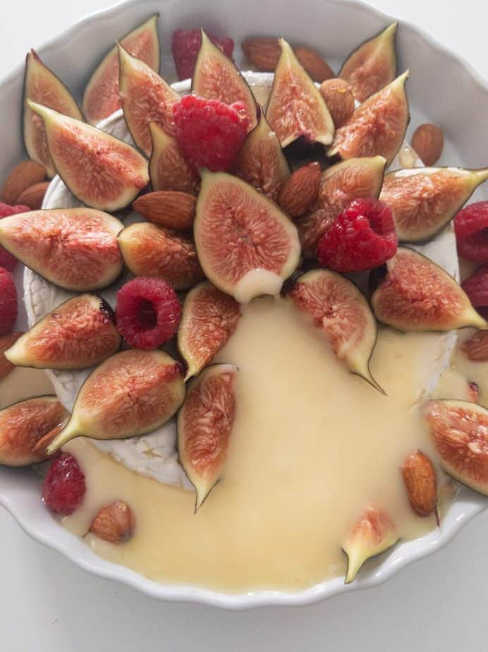 A pool of melted cheese spills out of a baked brie covered with figs, raspberries, and almonds.