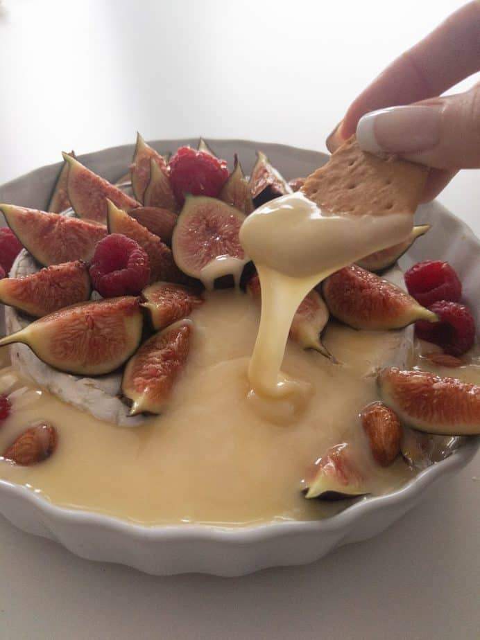 A hand dipping a cracker into melted brie.