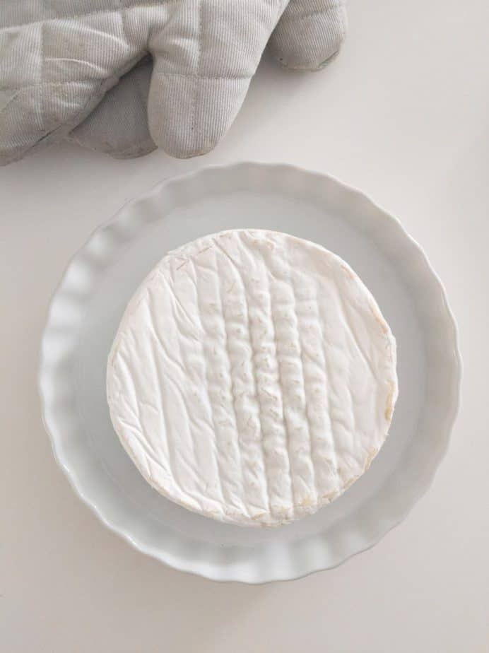 A wheel of brie in a baking dish beside a pair of oven mitts.