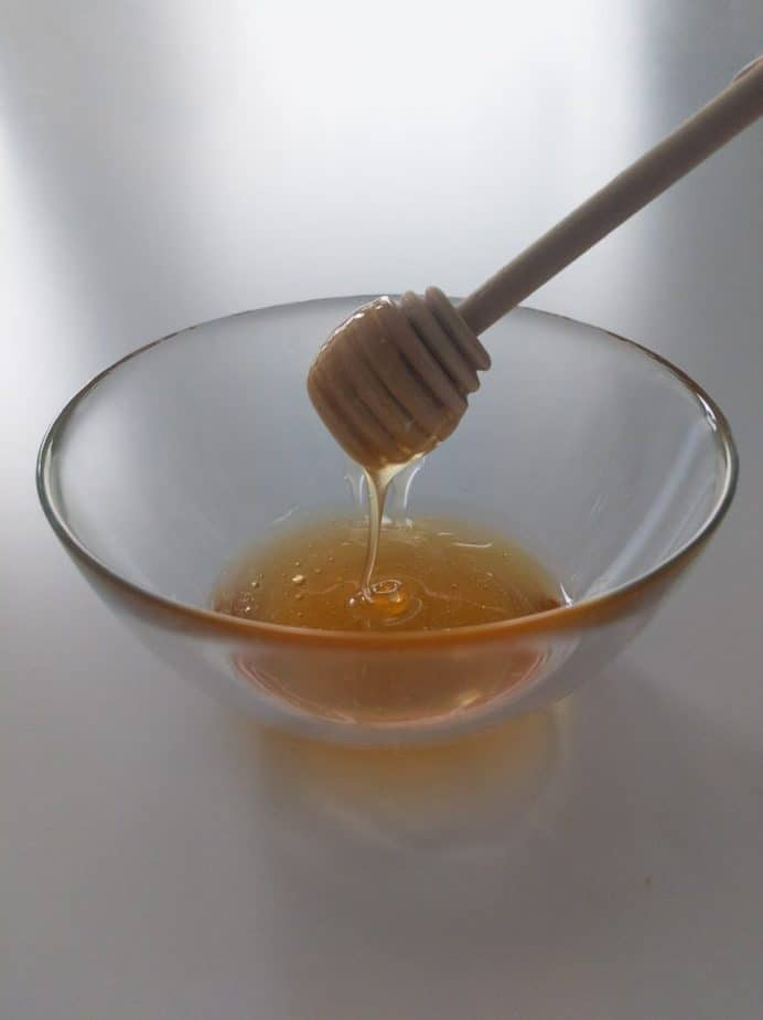 A honey stick lifting out of a bowl of truffled honey.