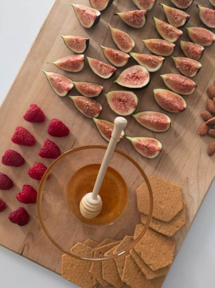 A wooden block arranged with the toppings: quartered figs, raspberries, almonds, truffled honey, and crackers for dipping.