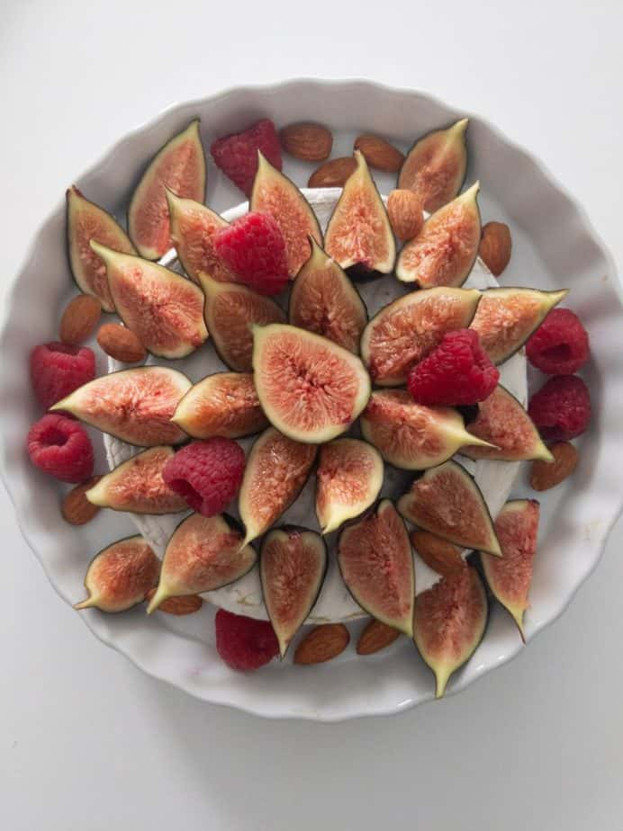 Cheese in a baking dish, covered with an arrangement of fig, raspberry, and almond toppings.