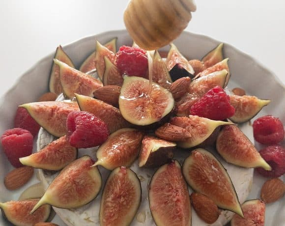 A honey stick drizzles truffled honey onto a baked brie covered with figs, raspberries, and almonds.