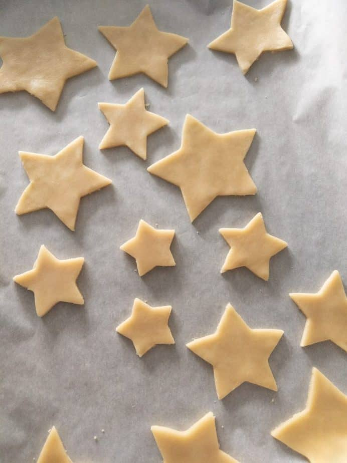 Star-shaped cookie dough on a parchment paper covered baking tray.
