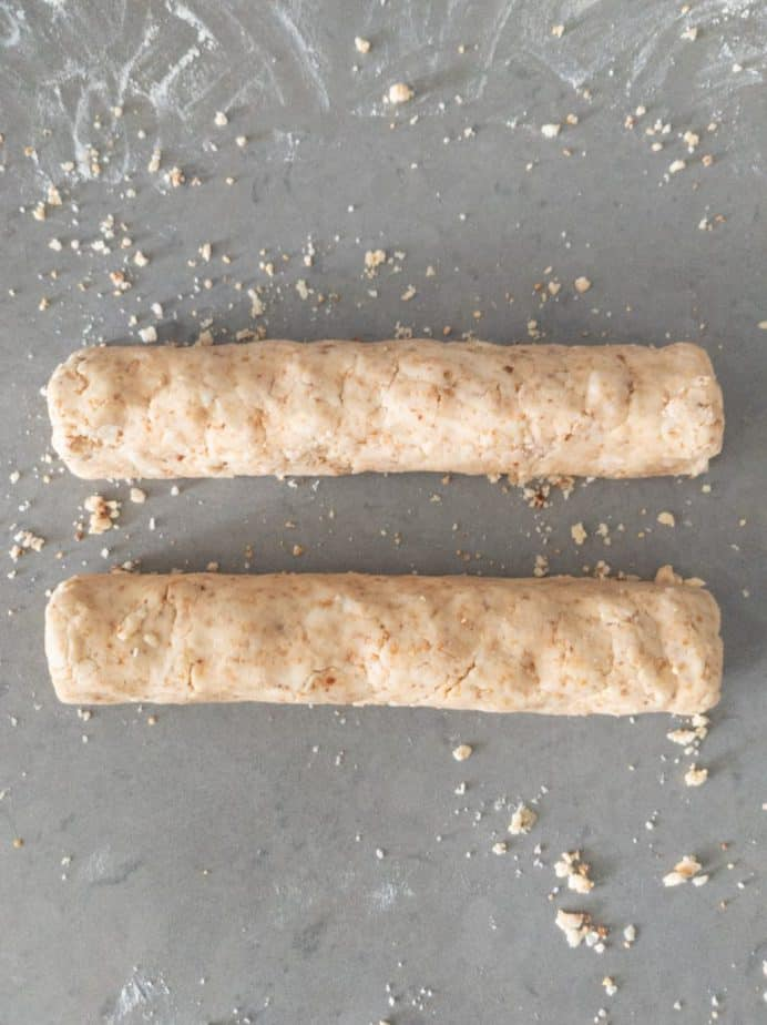 Two cylinders of cookie dough on a lightly floured surface.