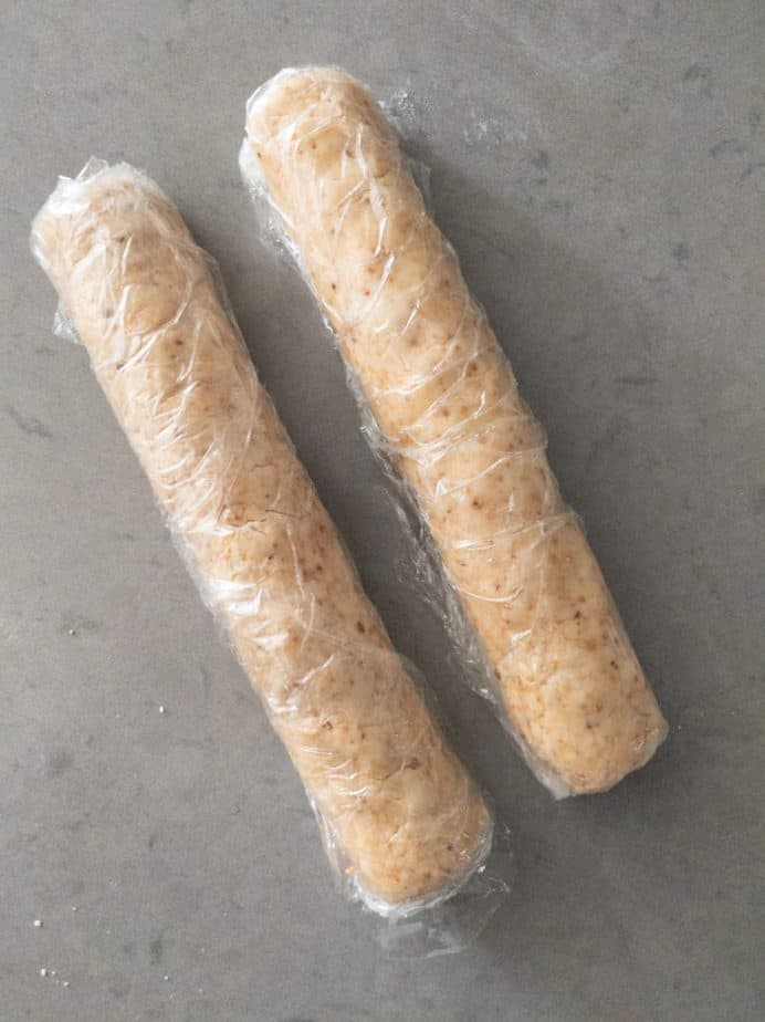 Cookie dough cylinders wrapped in plastic wrap.