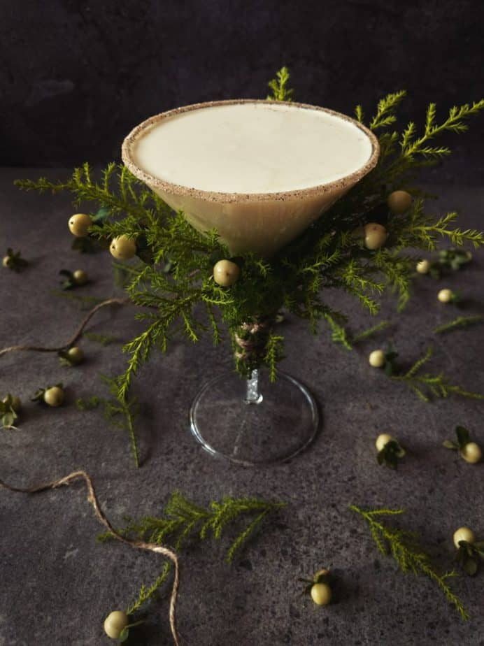 The turtle dove martini in a glass decorated with conifer branches and white berries.