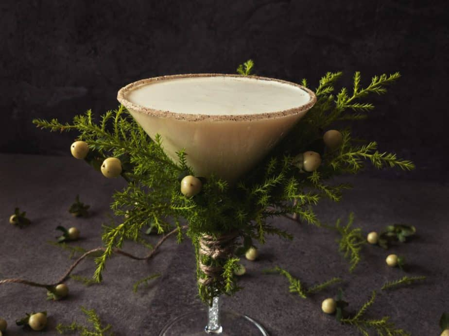 Turtle dove martini in a glass decorated with conifer branches and white berries.
