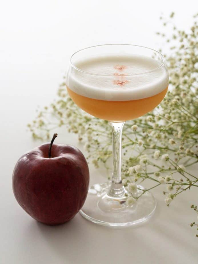 A cocktail glass beside an apple and flowers.