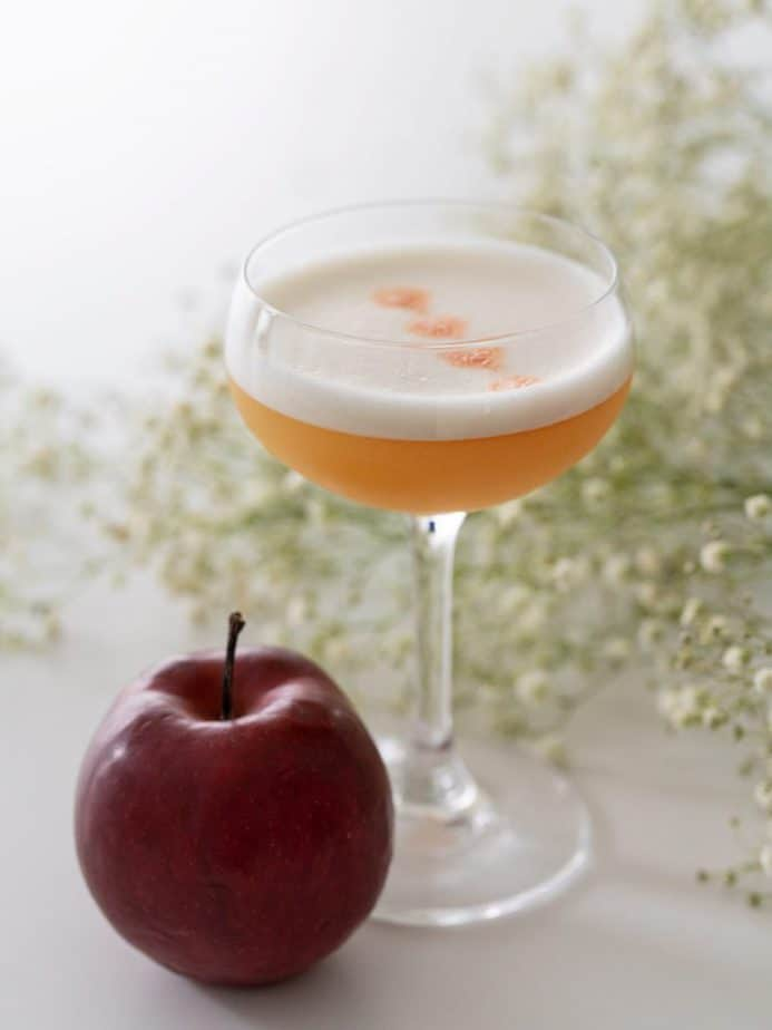 Profile view of an apple whisky sour and a red apple.