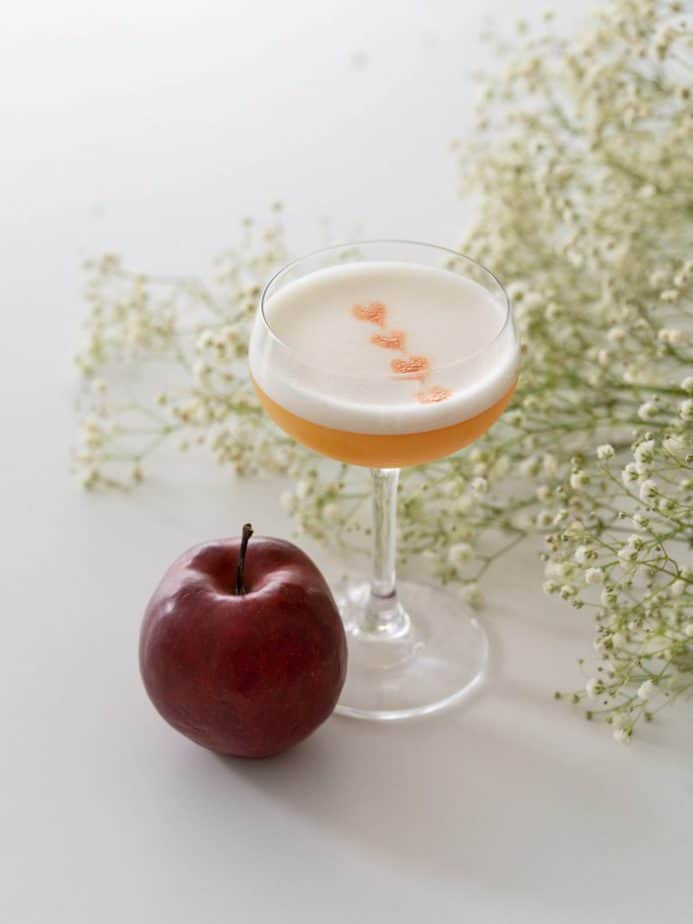 An apple whisky sour beside a red apple and white flowers.