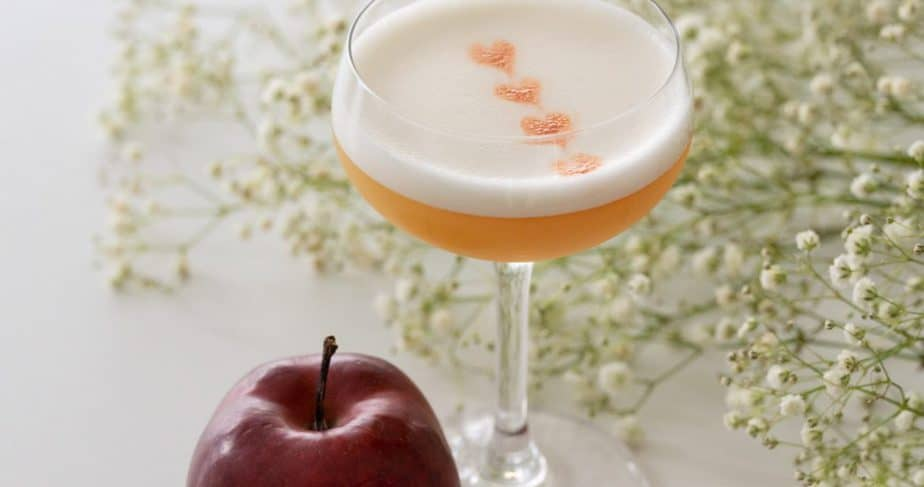 An apple whisky sour in a coupe glass by a red apple and small white flowers.