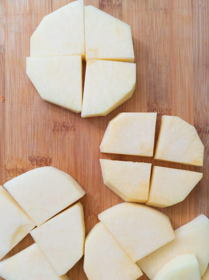 Peeled, sliced and quartered rutabaga pieces on a cutting board.